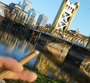 Hand smoking cigar by bridge